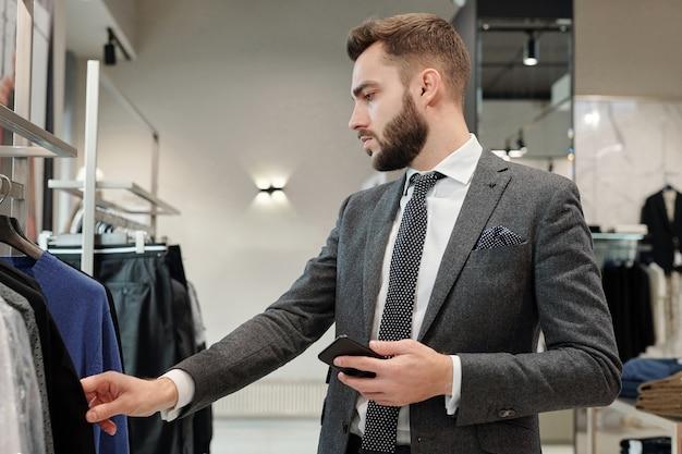 Grave empresario barbudo en elegante traje de pie en el estante y eligiendo ropa en la tienda