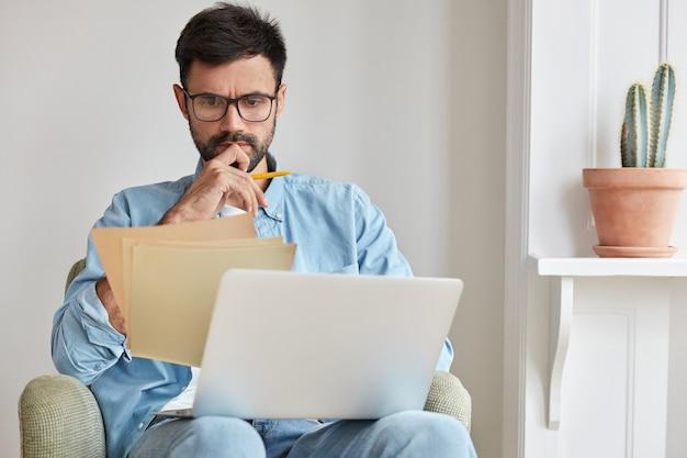 Grave empresario concentrado trabajando en casa