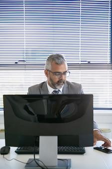 Grave empresario de pelo gris sentado en el lugar de trabajo con monitor de pc y tomando el teléfono móvil del escritorio. vista frontal. concepto de comunicación y multitarea