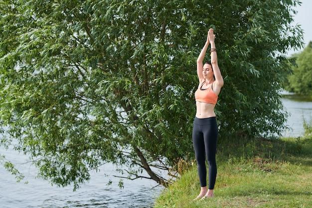 Grave hermosa joven en ropa deportiva de pie en la orilla y levantando las manos juntas mientras practica yoga