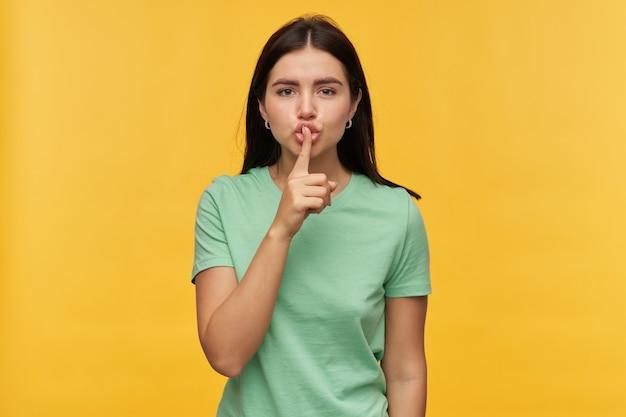 Grave hermosa morena joven en camiseta de menta se ve estricta y mostrando el signo de silencio aislado sobre la pared amarilla