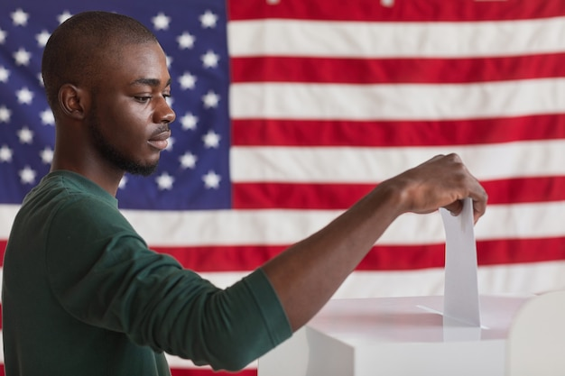Grave hombre africano poniendo la carta en la casilla durante la votación