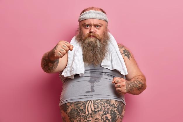 Grave hombre barbudo y regordete muestra los puños cerrados, sufre de sobrepeso, practica deporte, tiene el cuerpo sudoroso y los brazos tatuados, posa contra la pared rosada. concepto de adelgazamiento y dieta.