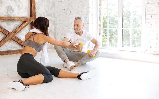 Grave hombre canoso sentado en el suelo y cruzando las piernas mientras mira a su instructor