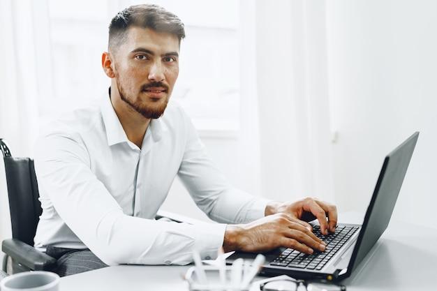Grave hombre concentrado en silla de ruedas usando su computadora portátil para trabajar / buscar trabajo en internet