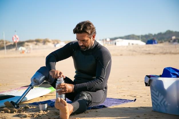 Grave hombre discapacitado sentado en la playa y abriendo termo
