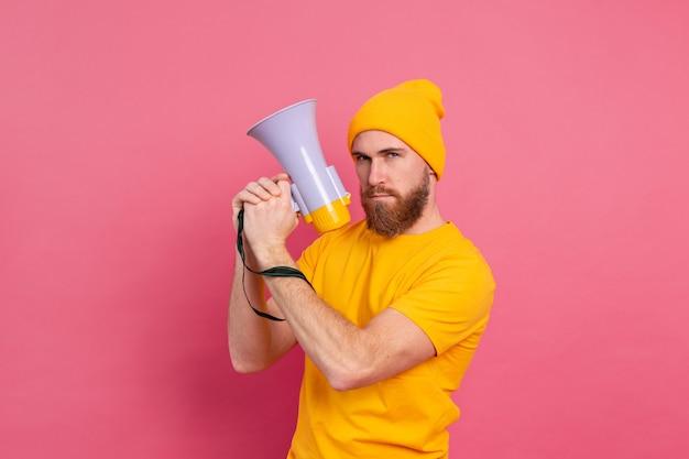 Grave hombre europeo con megáfono sobre fondo rosa