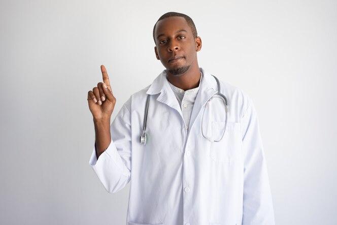 Grave hombre médico de pelo oscuro apuntando hacia arriba.