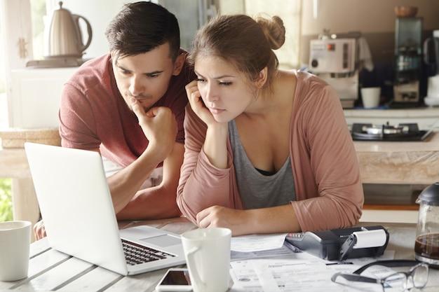 Grave hombre y mujer sentados en la mesa de la cocina frente a la computadora portátil abierta