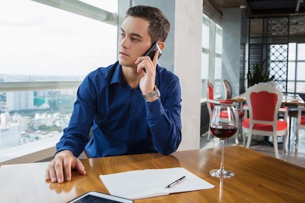 Grave hombre de negocios joven que habla en smartphone