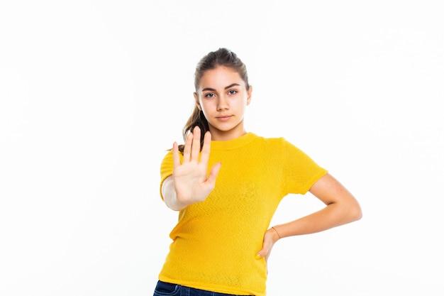 Grave joven adolescente en señal de stop haciendo casual en la pared blanca