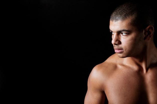Grave joven afroamericano desnudo de pie y mirando a otro lado
