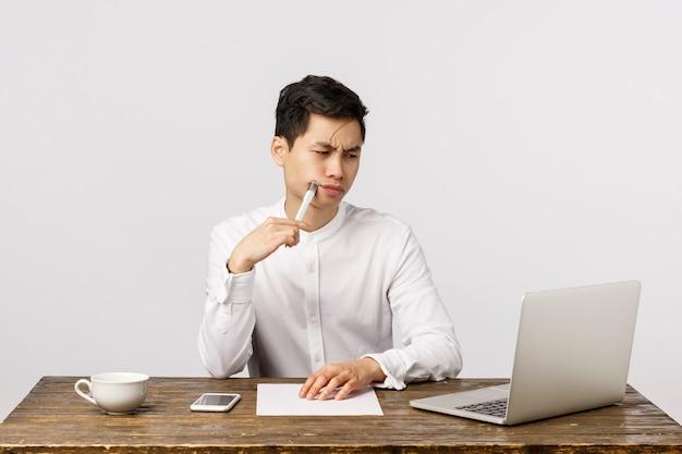 Grave joven asiático ocupado en el trabajo, sentado en el escritorio de la oficina, frunciendo el ceño perplejo, examinando gráficos en línea, mirando la pantalla de la computadora portátil, tocando los labios con un bolígrafo pensativo, escribiendo notas, informe para el jefe