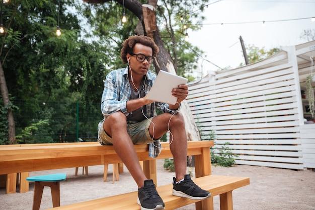 Grave joven en auriculares escuchando música y usando tableta al aire libre