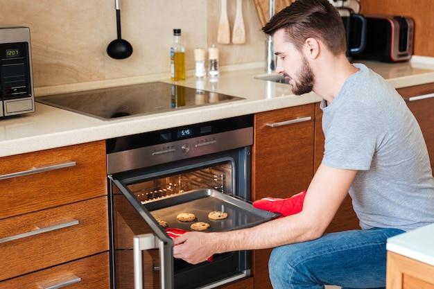 Grave joven barbudo para hornear galletas en el horno en la cocina