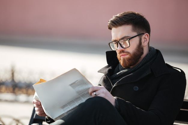 Grave joven barbudo sentado y leyendo el periódico al aire libre