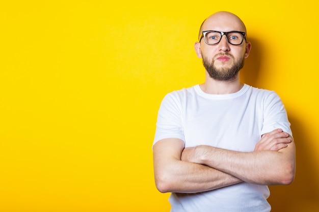 Grave joven calvo con barba en gafas con una camiseta blanca