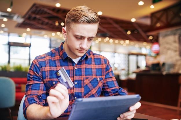Grave joven con el ceño fruncido sentado en la mesa de café con una computadora de mesa y pagando compras en línea con tarjeta de crédito