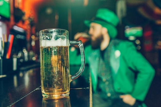 Grave joven concentrado en traje de san patricio sentado en la barra de bar en pub solo. una jarra de cerveza se para frente a él más cerca de la cámara.