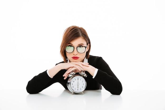 Grave joven dama de negocios con gafas con reloj despertador