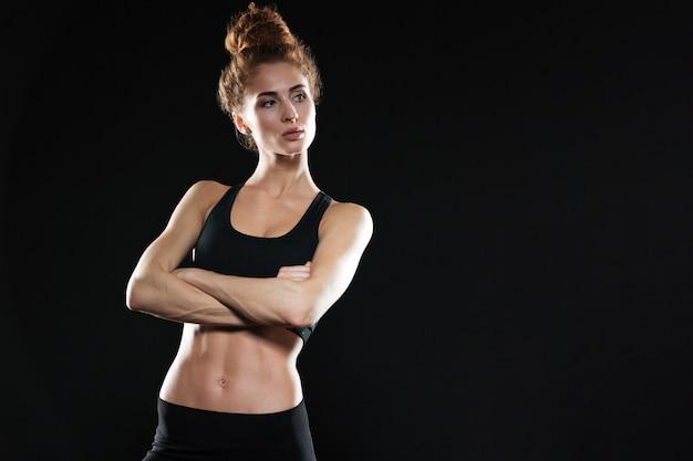 Grave joven deportiva posando con los brazos cruzados