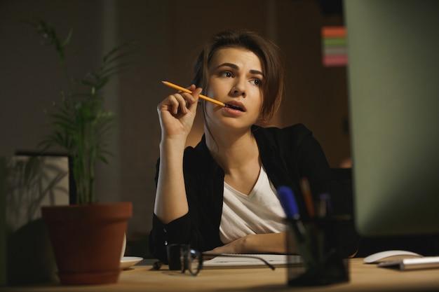 Grave joven diseñadora sentada en la oficina por la noche