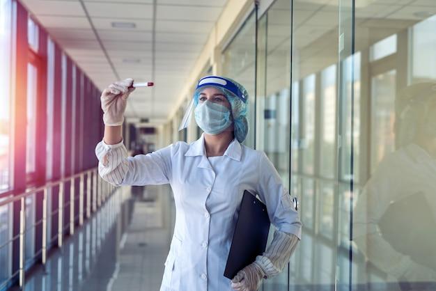 Grave joven doctora con protector facial mirando sangre positiva para el resultado covid-19.