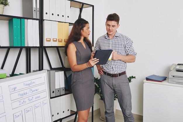 Grave joven empresaria mostrando informe sobre tableta a colega y pidiendo su opinión