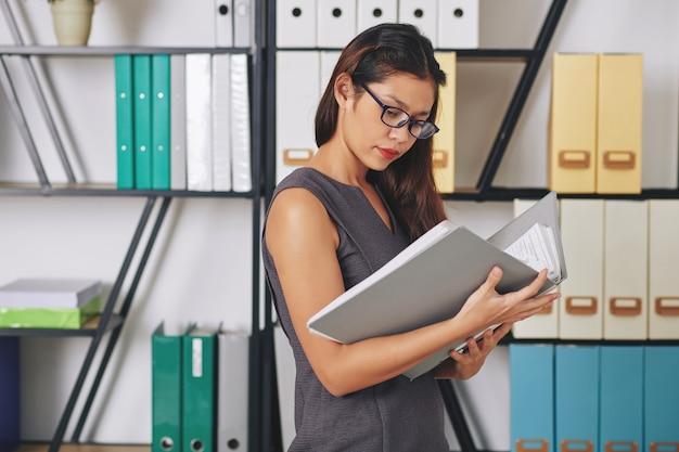Grave joven empresaria en vasos de pie en el archivo de la oficina y buscando documentos en una carpeta gruesa