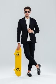 Grave joven empresario en sunglaasses y traje apoyado en patineta con las piernas cruzadas sobre la pared gris