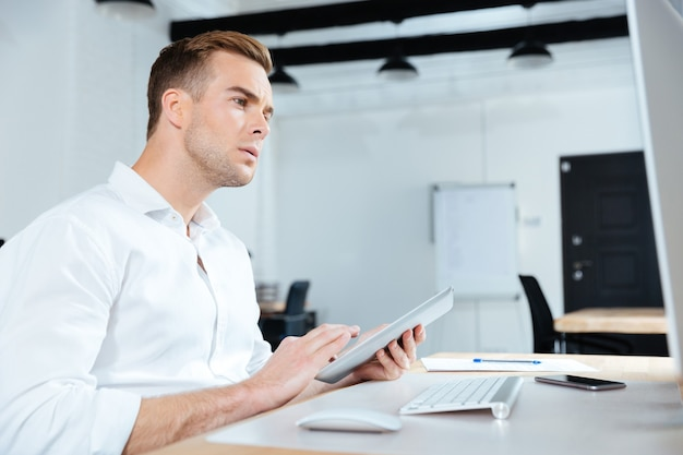 Grave joven empresario con tableta y computadora en la oficina