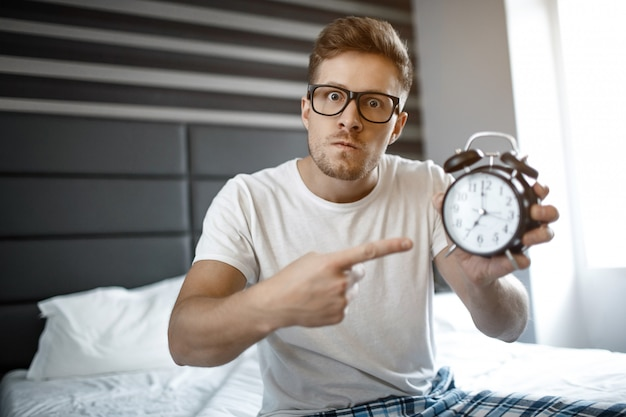 Grave joven enojado en la cama por la mañana. él mira a la cámara y señala el reloj.