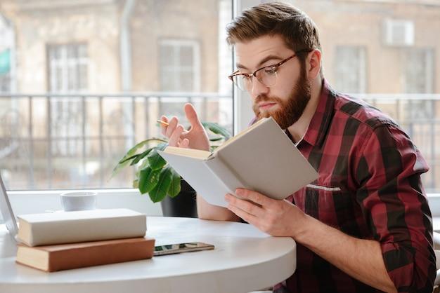 Grave joven leyendo libros mientras usa la computadora portátil
