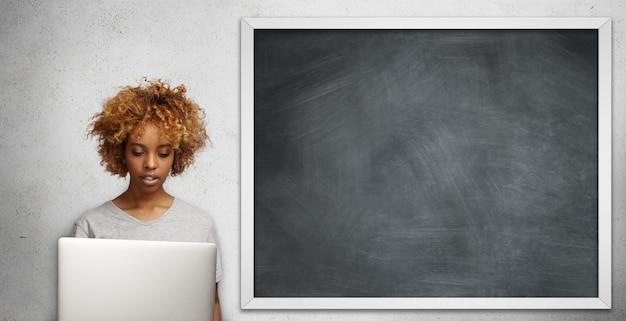 Grave joven maestra de piel oscura con anillo en la nariz vestida de manera informal usando una computadora portátil para trabajar en clase, revisando papeles, haciendo un plan educativo, mirando la pantalla con expresión enfocada