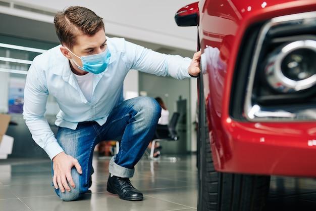 Grave joven en máscara médica comprobando los neumáticos del coche en el concesionario