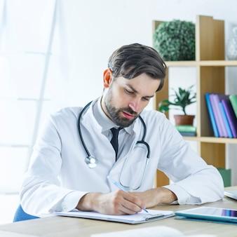 Grave joven médico escribiendo receta