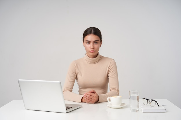 Grave joven mujer morena de ojos azules que trabaja en la oficina moderna con una computadora portátil, manteniendo los labios doblados mientras mira, vestida con ropa formal mientras posa sobre una pared blanca