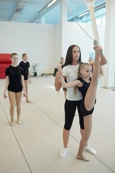 Grave joven profesora de porristas con cabello castaño apoyando a la niña mientras ella hace split vertical en el gimnasio