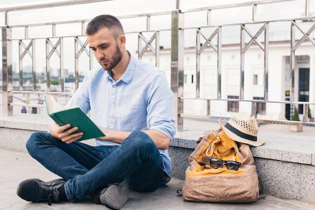 Grave joven sentado cerca de la baranda al aire libre y leyendo el libro