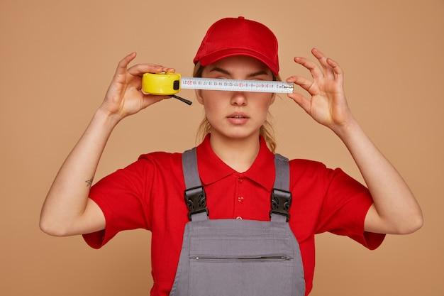 Grave joven trabajador de la construcción con gorra y uniforme sosteniendo el medidor de cinta delante de sus ojos