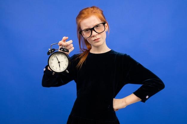 Grave jovencita pelirroja con gafas en un vestido negro tiene un gran despertador azul