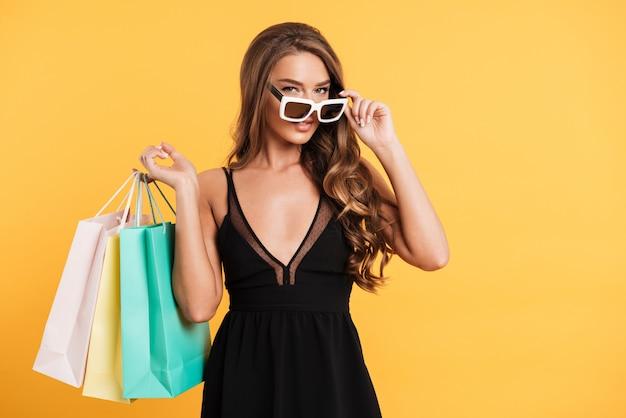 Grave jovencita en vestido negro con bolsas de compras.
