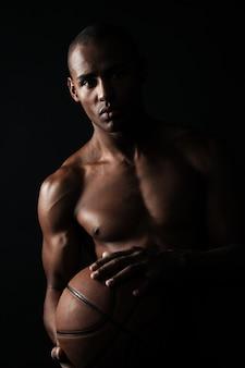 Grave jugador de baloncesto afroamericano sosteniendo la pelota,