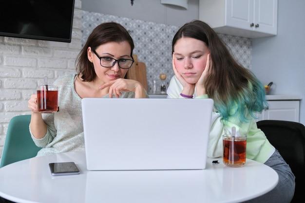 Grave madre e hija adolescente sentada en casa en la mesa, mirando la computadora portátil. información desagradable, video triste e infeliz