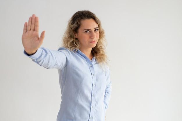 Grave mujer descontenta haciendo gesto de parada