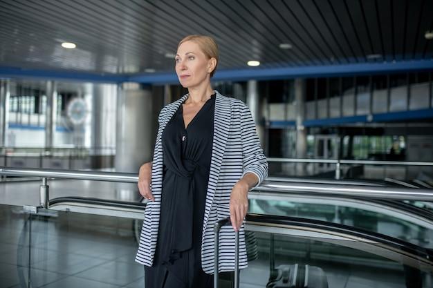 Grave mujer elegante con maleta en la terminal del aeropuerto