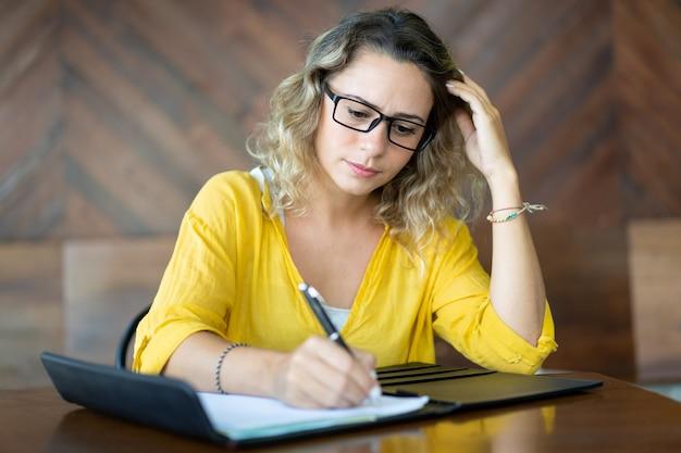 Grave mujer emprendedora escribiendo ideas para el proyecto de inicio
