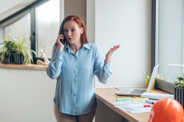 Grave mujer gesticulando hablando por teléfono inteligente