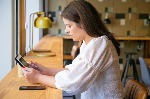 Grave mujer joven y bonita en camisa blanca con tableta mientras está sentado en el escritorio en el espacio de trabajo conjunto o cafetería