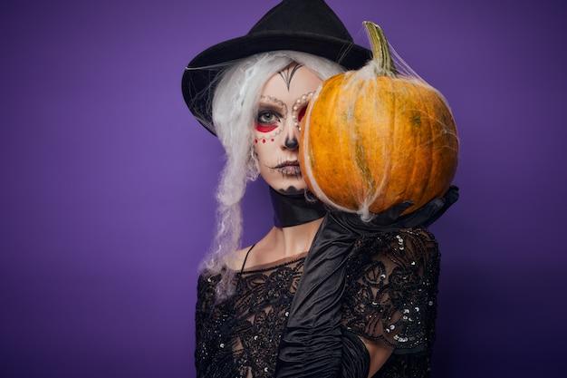 Grave mujer joven con maquillaje de halloween cubre la mitad de la cara con calabaza